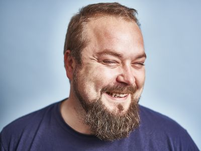close-up of laughing man in his early 30s with a beard