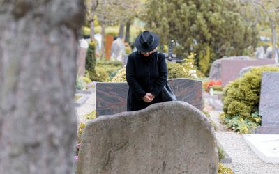 Senior Woman Standing By Tombstones In Cemetery
