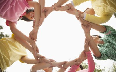 group of kids linking arms in a circle