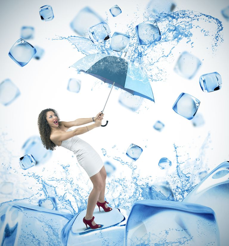 Woman with umbrella and raining ice cubes
