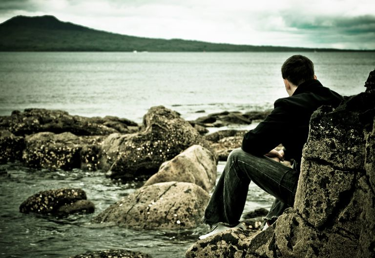 a man looking at the ocean sitting on a rock