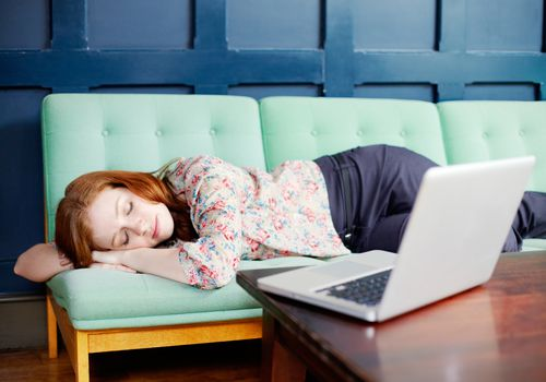 Woman asleep on sofa next to laptop on coffee table