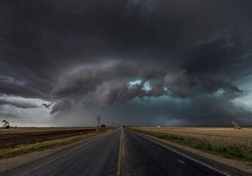 Tornado clouds forming over a highway