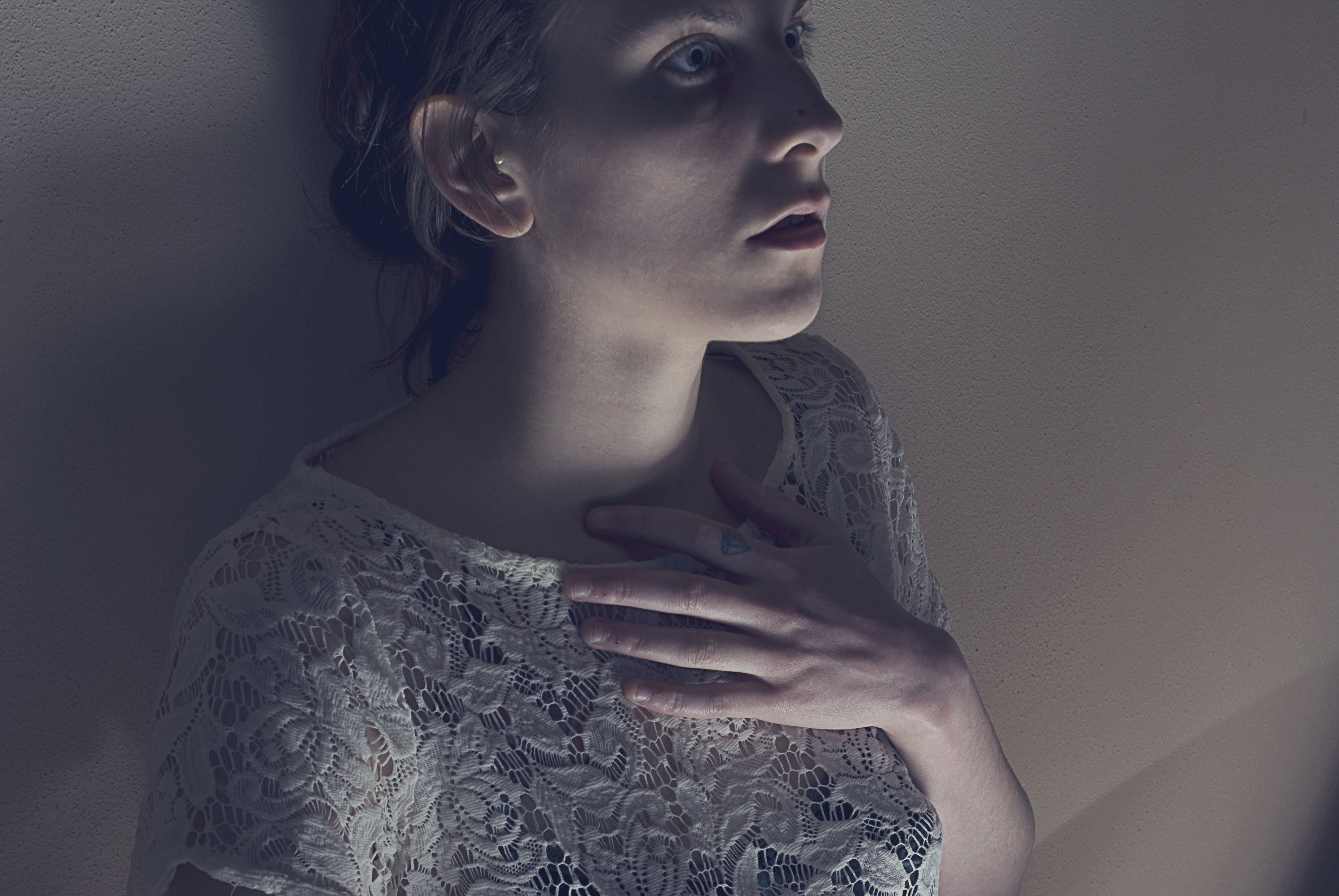 Scared woman leaning against a wall