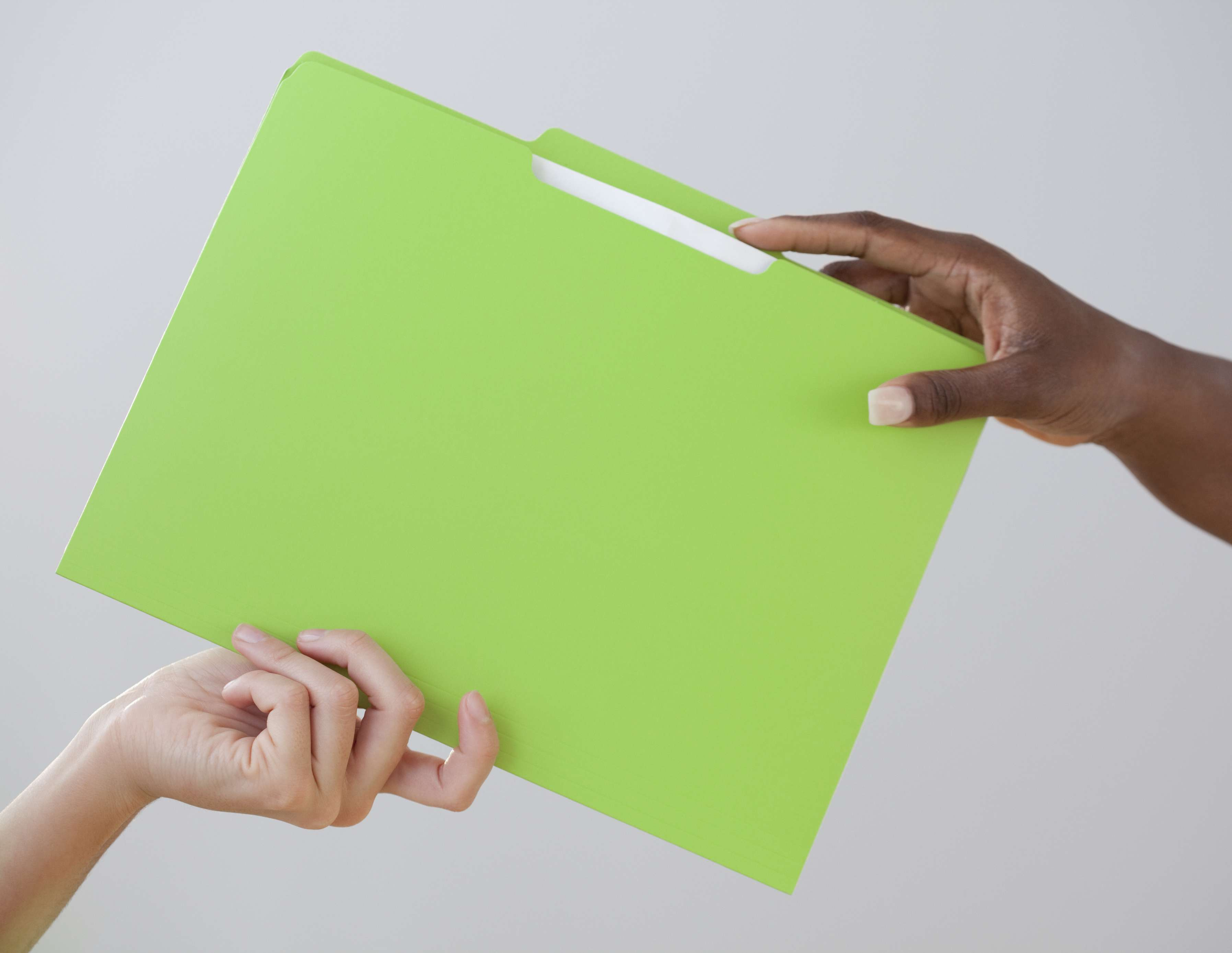 Hand passing a folder to another person's hand