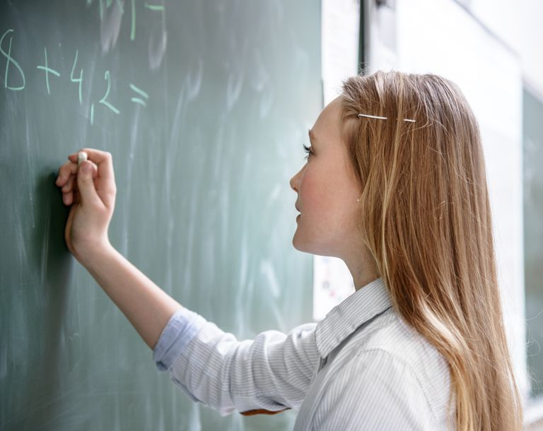 A schoolgirl doing mathematics at chalkboard
