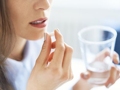 Woman taking pill with a glass of water