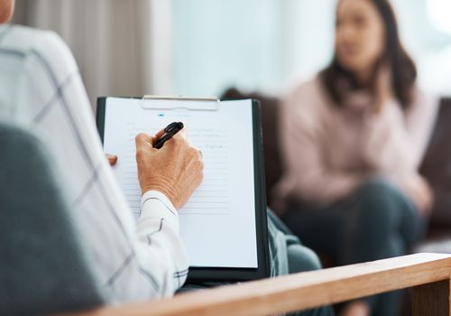 Cropped shot of a psychologist writing notes during a therapeutic session with her patient