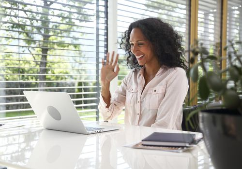 Woman waving in a Zoom meeting