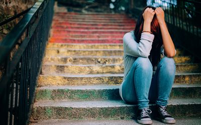 Woman sitting on steps with head in her hands