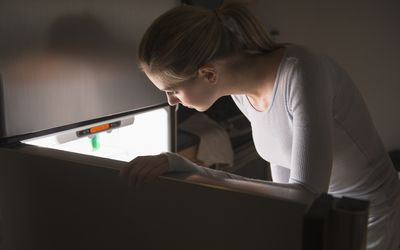 Woman opening fridge at night