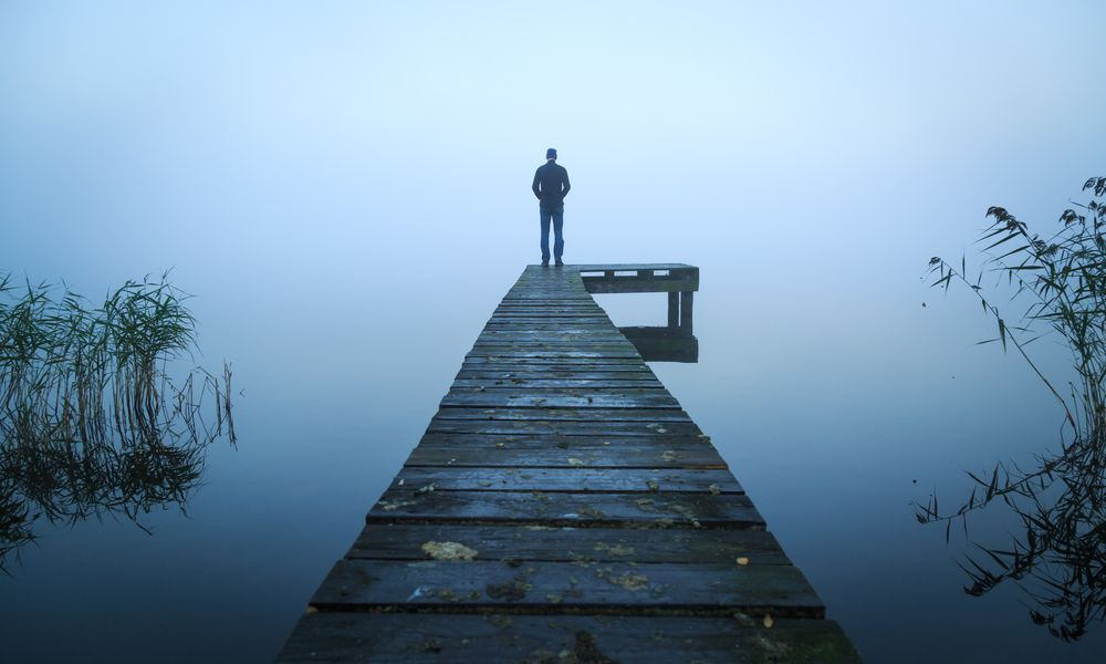 Depressed man standing alone on a jetty on a foggy autumn day