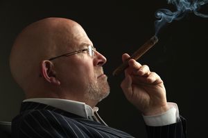 Bald headed businessman smoking a cigar