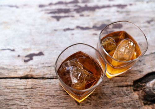 Two glasses of dark liquor side by side on wood table