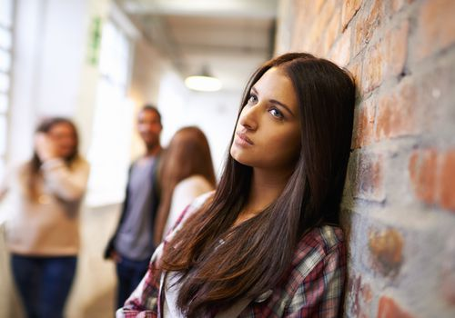 Sad woman leaning against a wall in a hallway