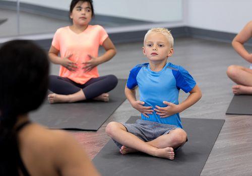 Young children practice breathwork in yoga class.