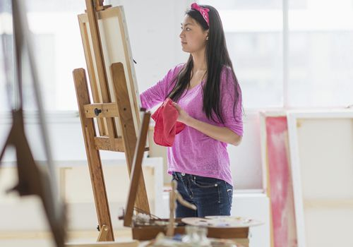 A teenage girl painting in a studio.