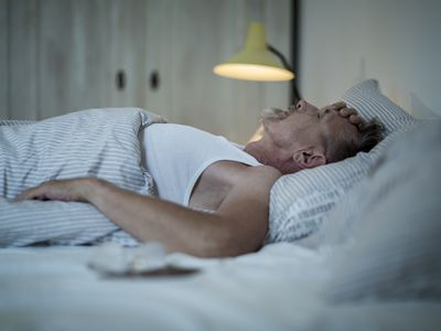 Senior man in his early 60s with greying beard is sick and sleepless in bed while night.