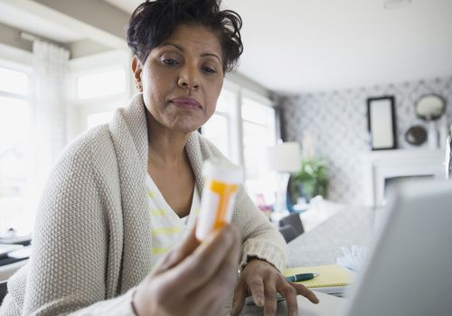 A woman examines her bottle of medication.