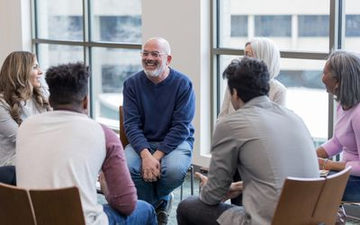 Diverse people sit in circle and brainstorm ideas