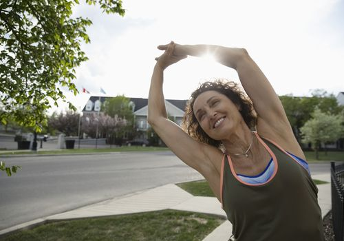 Smiling woman stretching arms on sunny neighborhood sidewalk
