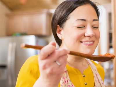 Woman tasting sauce from a wooden spoon