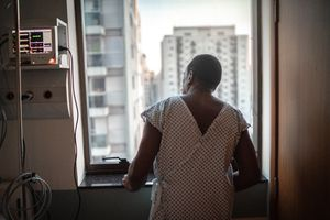 Senior patient looking through window at hospital