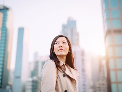 Confident young Asian woman looking up to sky with smile on a fresh bright morning against city skyline