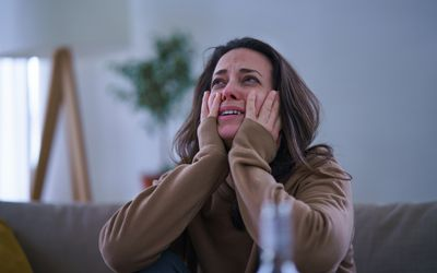 Woman crying with head in hands.