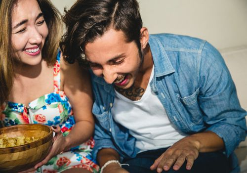 Cheerful young friends laughing sitting on sofa at party snacking