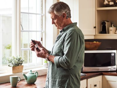 Man looking at a bottle of cannabidiol.