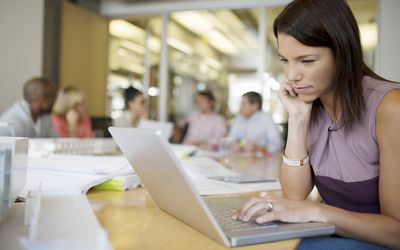 Woman using laptop in business meeting.