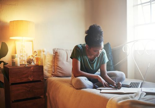 Female college student does schoolwork on a bed