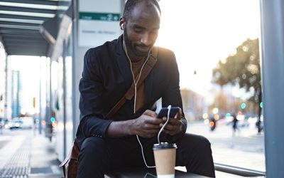 Young businessman sitting at tram stop in the evening using earphones and smartphone