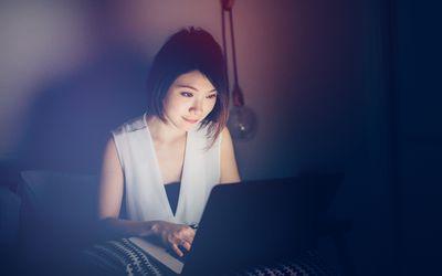 woman using laptop in a darkened room