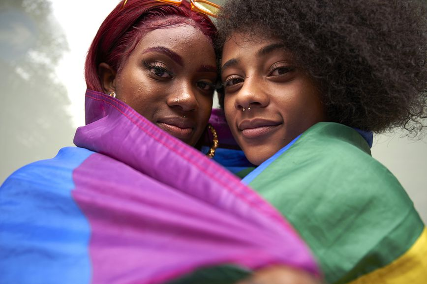 two women wrapped in a pride flag