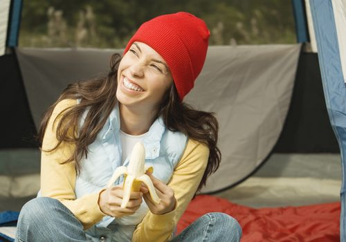Close-up of a young woman peeling a banana