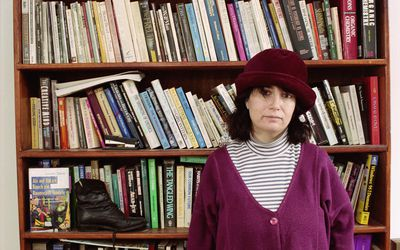 a woman standing in front of a bookshelf full of books