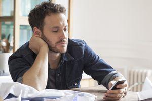 Man looking at phone, appearing bored.