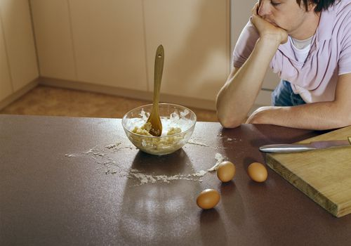 Young man looking at dough in a mixing bowl on the kitchen counter