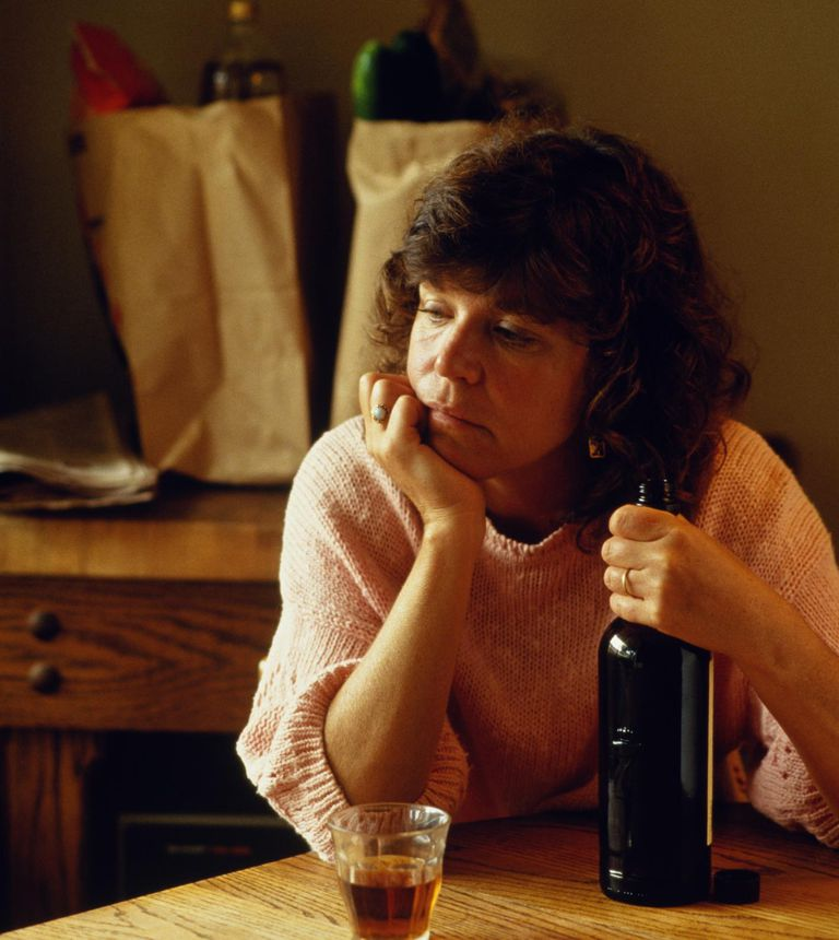 Woman Drinking in Kitchen