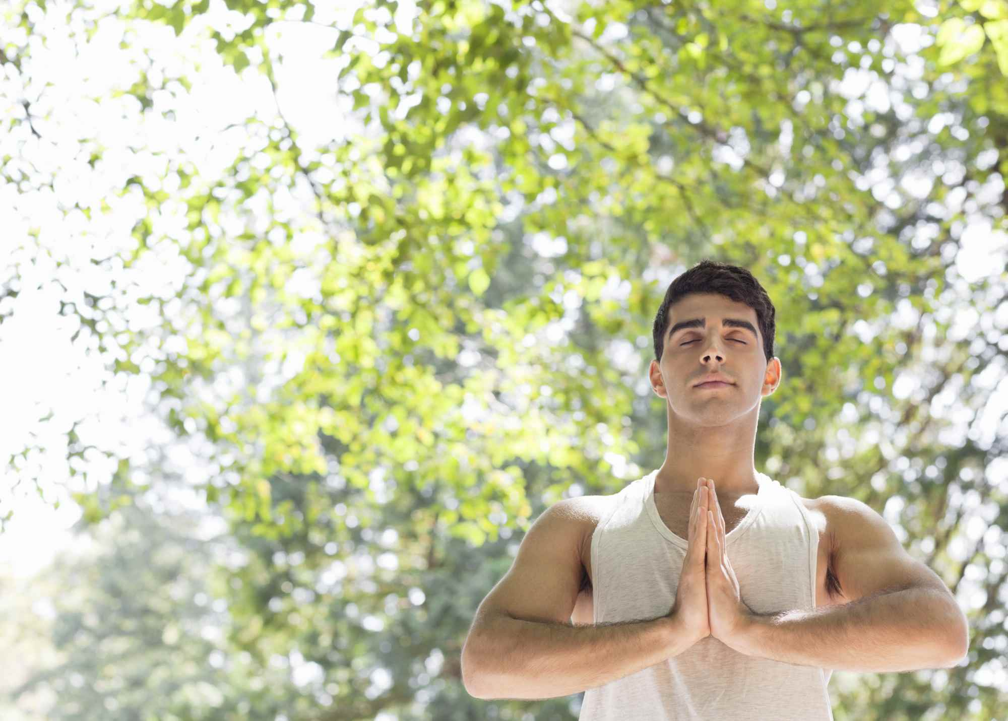 Close up of man practicing yoga in woods