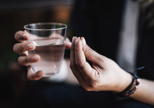 Person with a pill in hand and a glass of water.