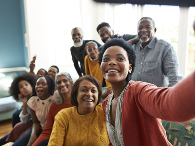 Young woman taking selfie with family and friends