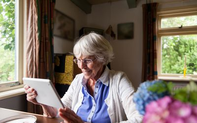 older woman holding an ipad