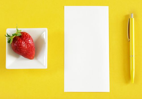 Top view of table with blank paper, strawberry and pen