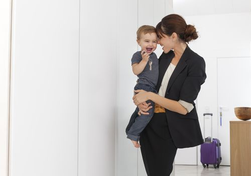 Woman in suit holding toddler boy on her hip and rolling luggage near door behind her