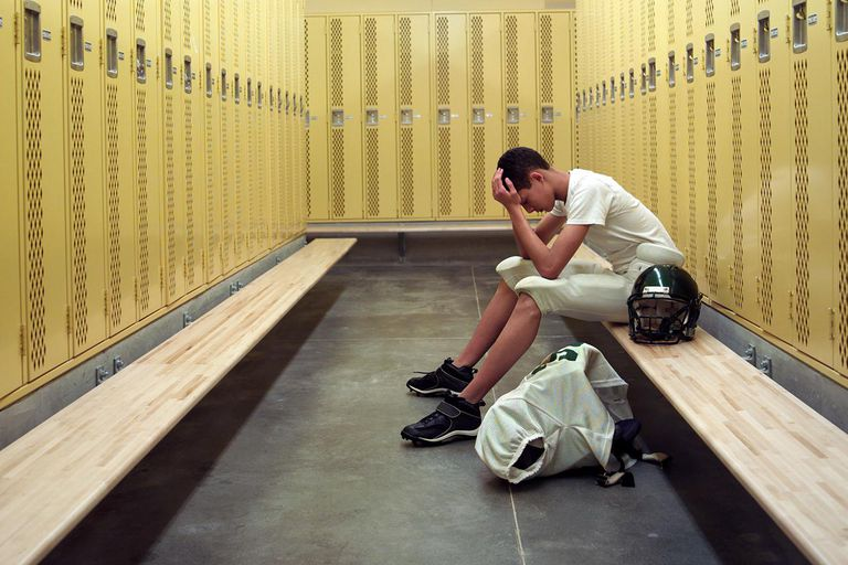 Teenage boy (15-17) in football uniform, sitting in locker room
