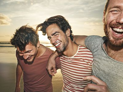 Three male friends on beach, smiling - stock photo