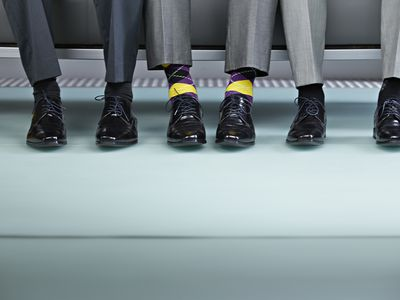 shot of 3 pairs of men's legs and shiny black shoes
